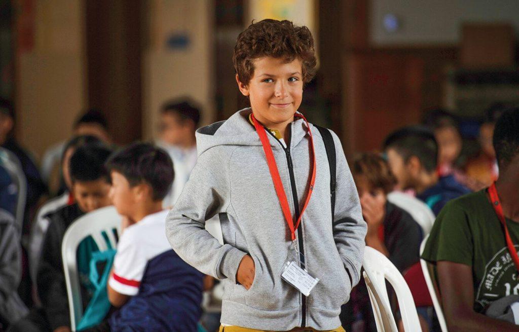 Студент Young Learner улыбается в камеру в зале для собраний