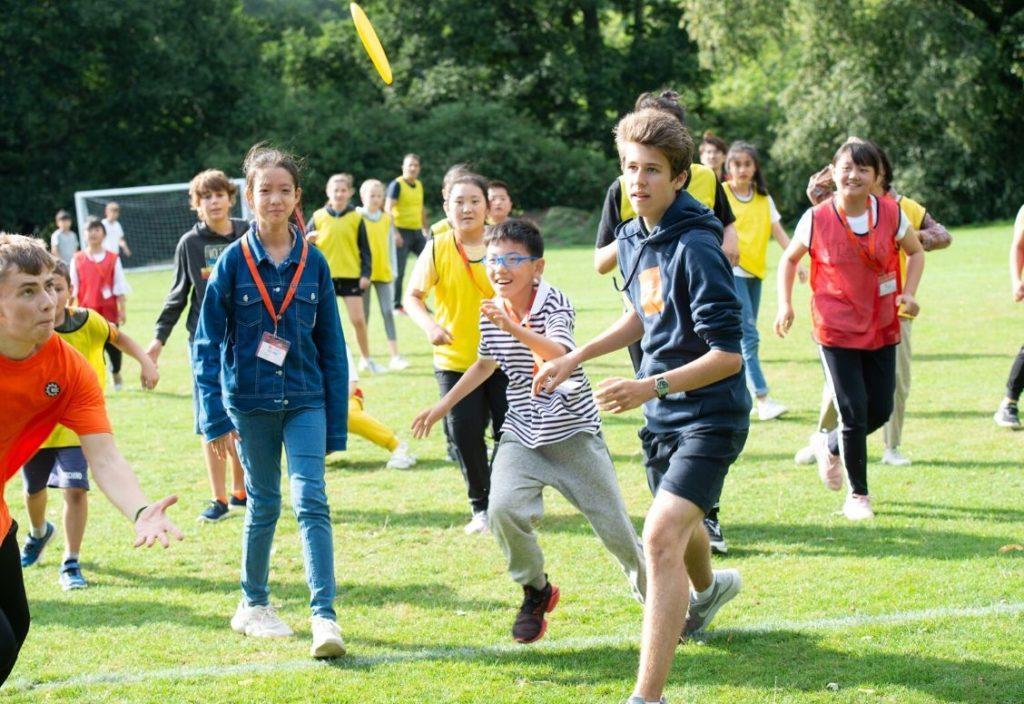 Большая группа детей, увлеченных спортивными играми на свежем воздухе