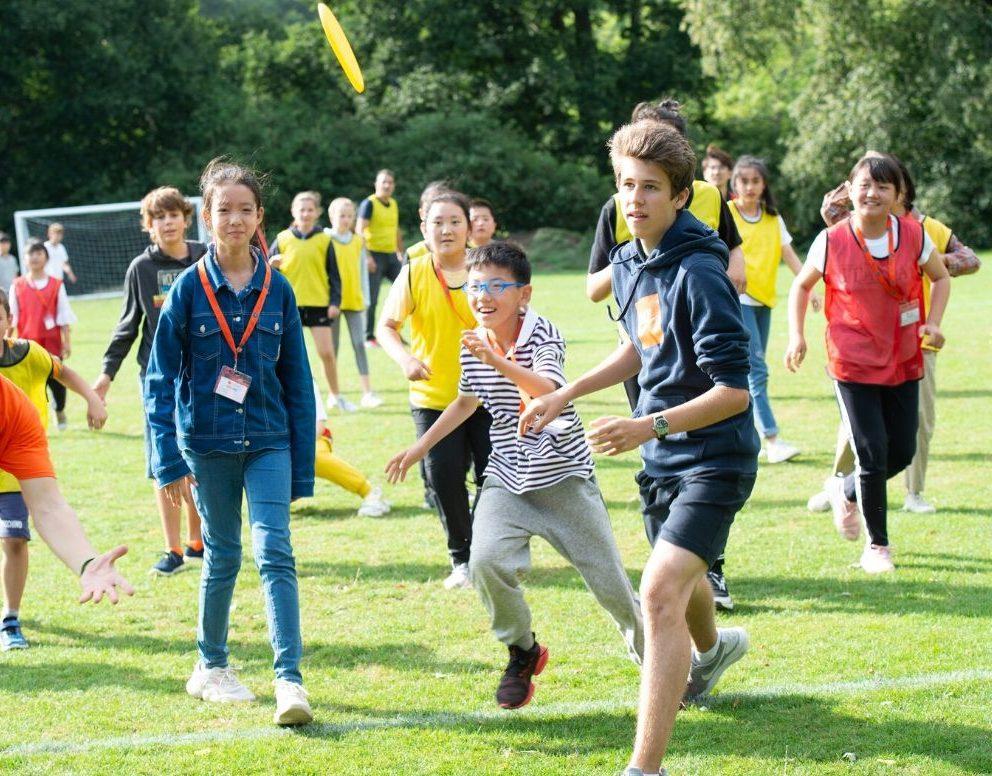 Большая группа детей увлечены спортивными играми на свежем воздухе
