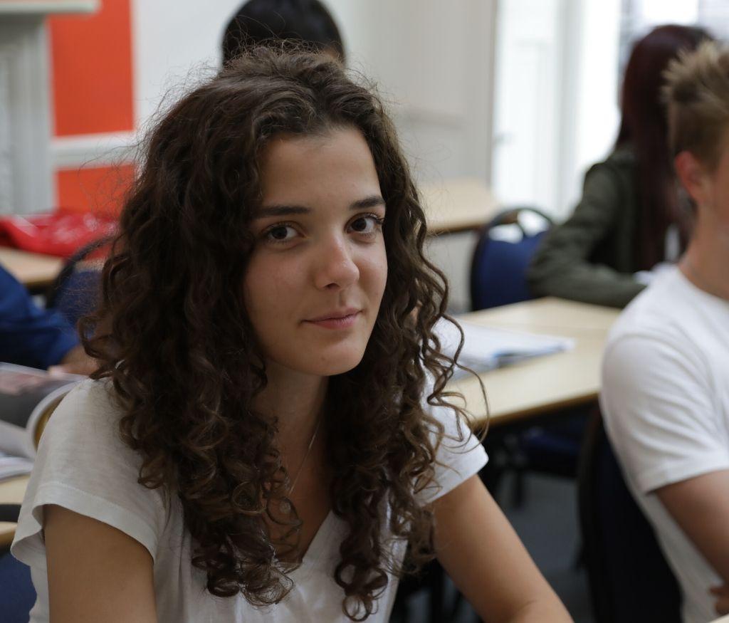 Студент в классе смотрит в камеру