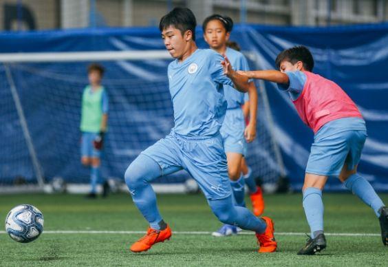 Мальчики борются за мяч на крытом поле