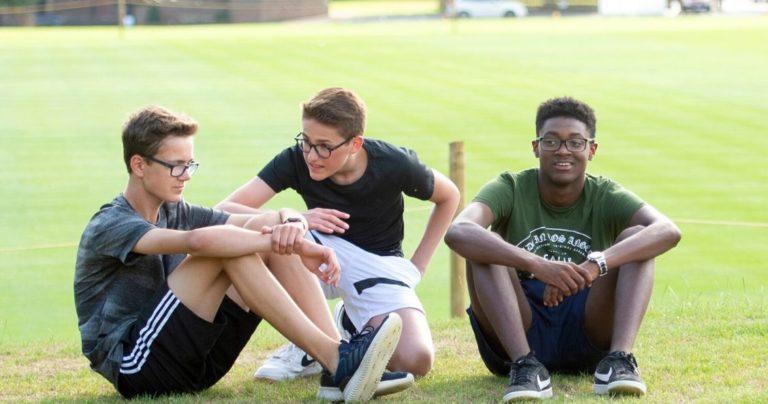 Три мальчика в спортивных костюмах сидят на траве