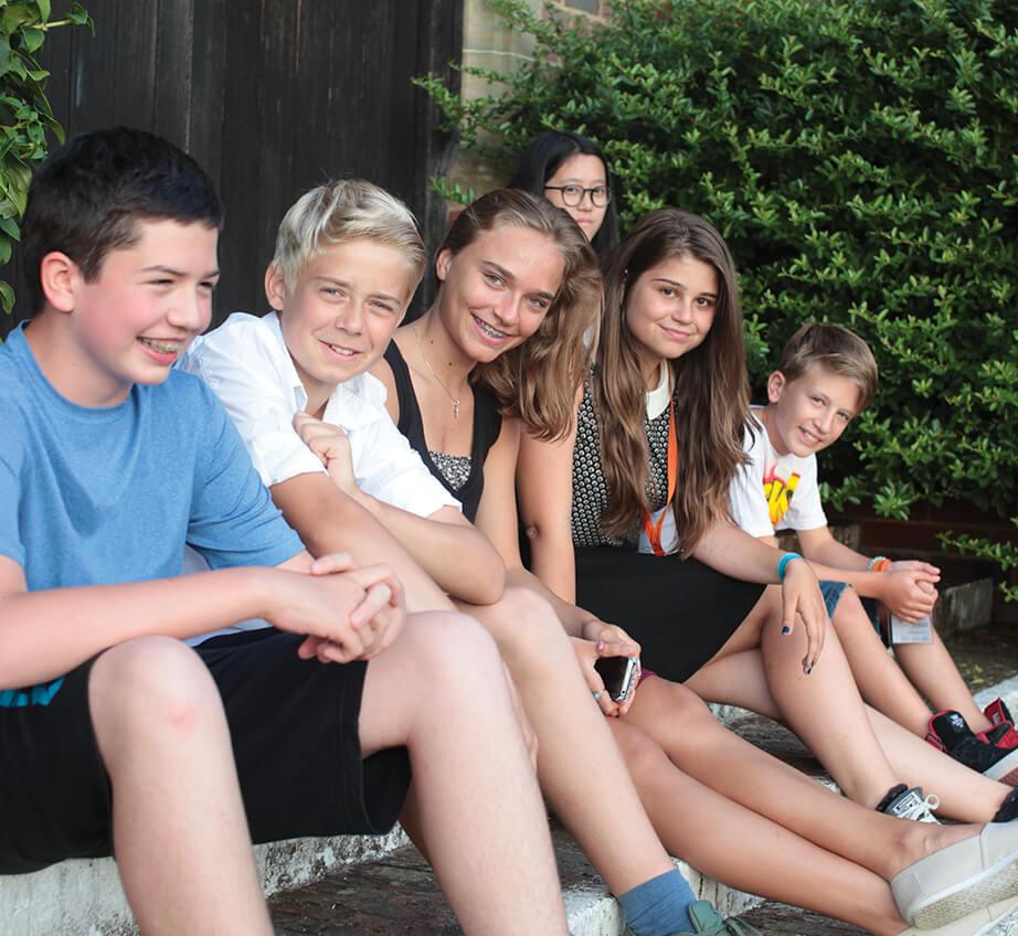 Группа юных учеников сидит на ступеньках