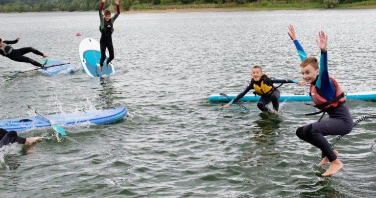 Серфингисты, учащиеся школы, прыгают с досок в озеро