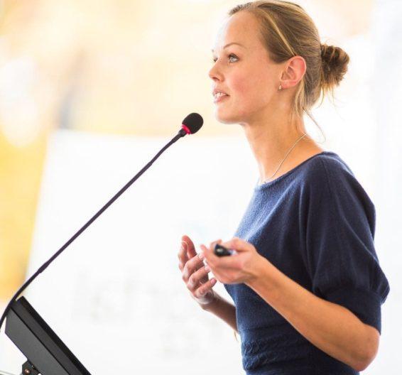 Женщина со светлыми волосами выступает перед микрофоном