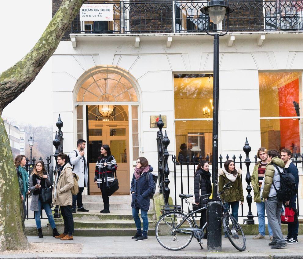 Группа студентов стоит у здания BSC в Лондоне
