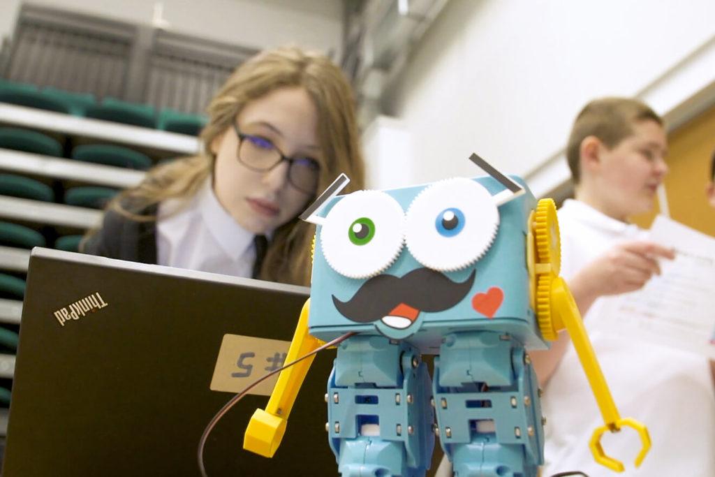 Девочка смотрит через ноутбук на робота в лагере программирования и робототехники