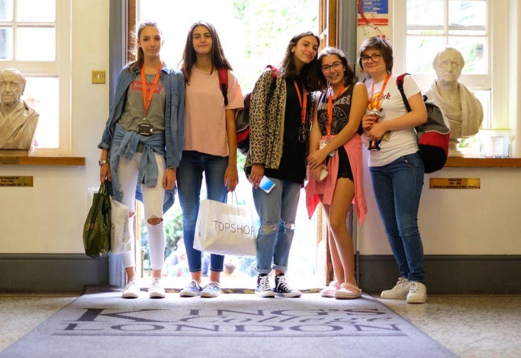 Группа девочек с пактами с модными покупками стоит в дверях Королевского колледжа в Лондоне
