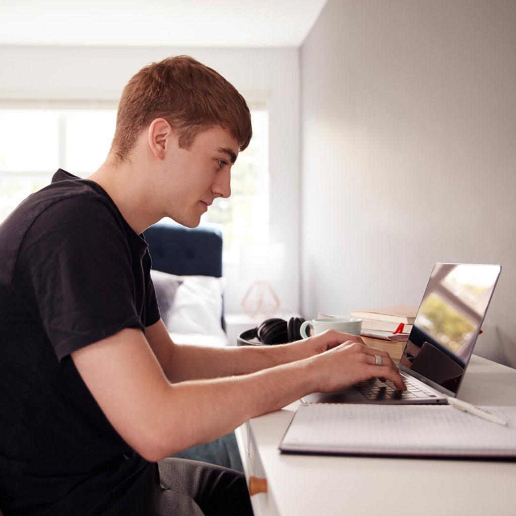 Студент работает за ноутбуком дома