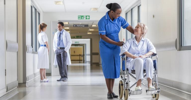 Медицинский работник разговаривает с пациентом в больнице