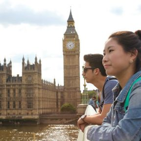 Two students lean over a bridge with Big Ben and the houses of parliament in the background
