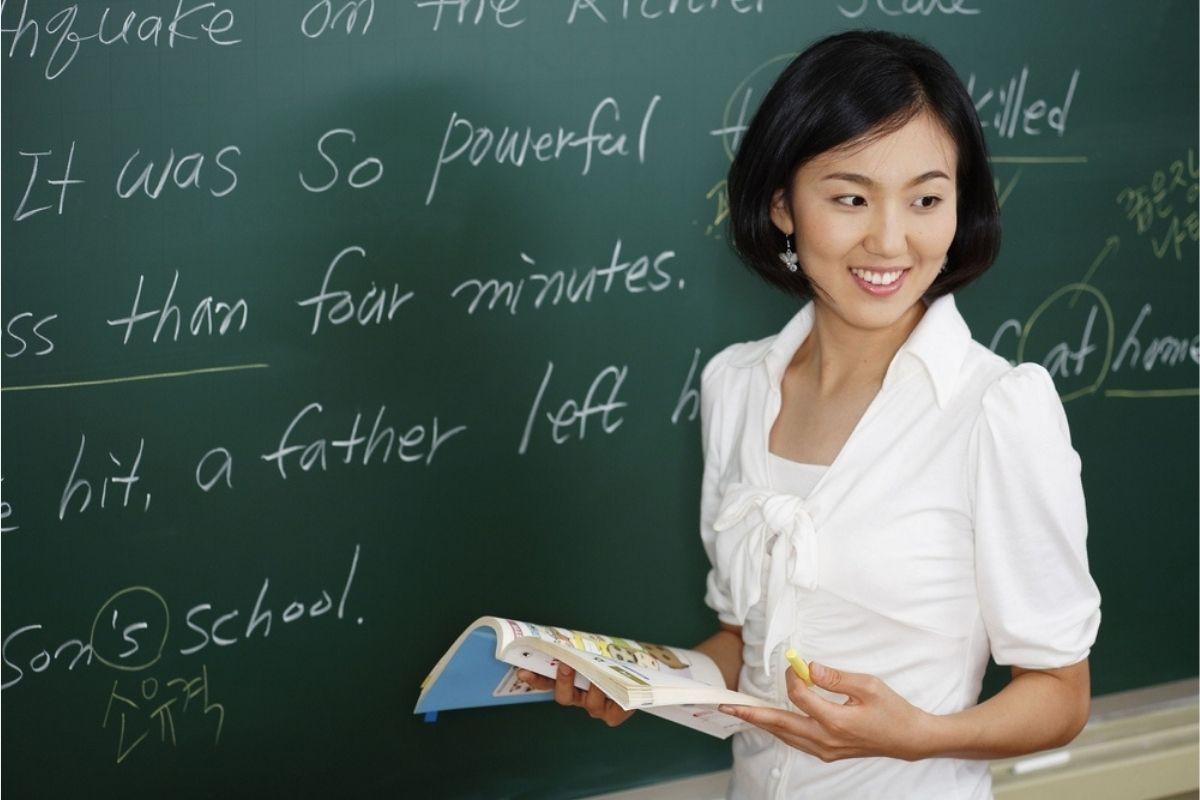 Asian lady learns English by blackboard