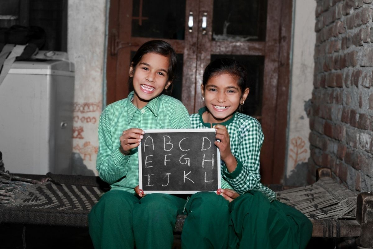 Two smiling children learn English