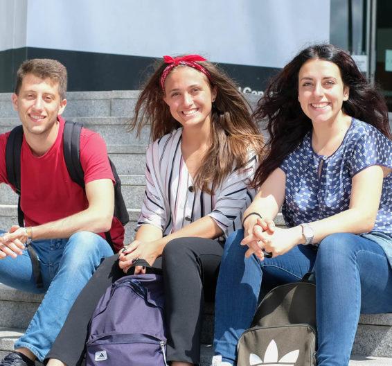 Três alunos sorridentes sentados nos degraus do lado de fora da sede do Facebook em Dublin