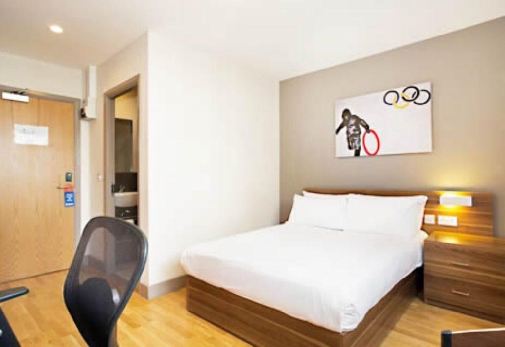 Grande quarto com pisos de madeira, cama de casal e cadeira para mesa