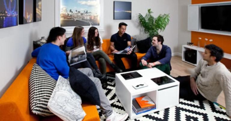 Grupo de alunos conversando na sala de estar de uma acomodação
