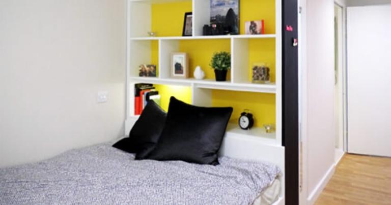 Quarto com lençóis cinza e paredes amarelas.