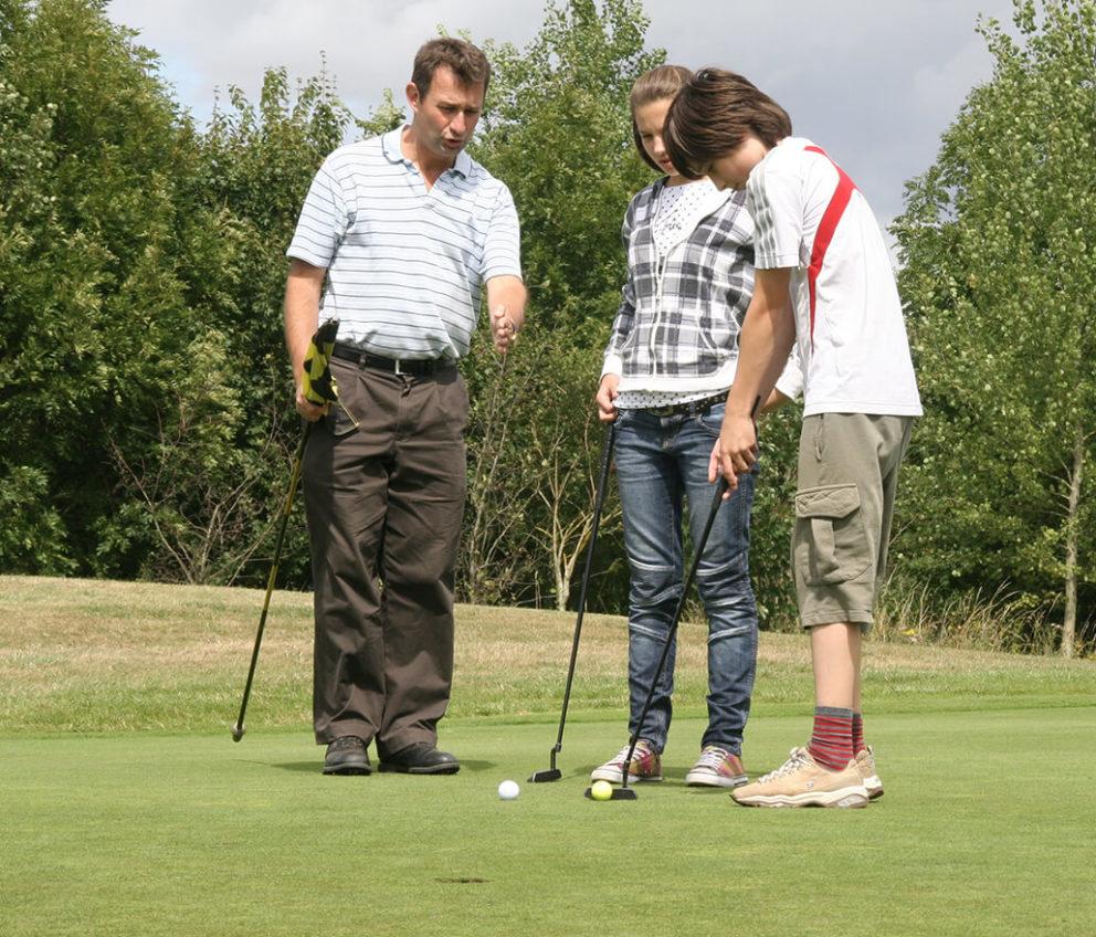 Um adulto e duas crianças jogando golfe em Edimburgo.