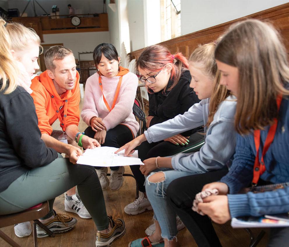Um grupo de jovens estudantes escutando o líder de um campo