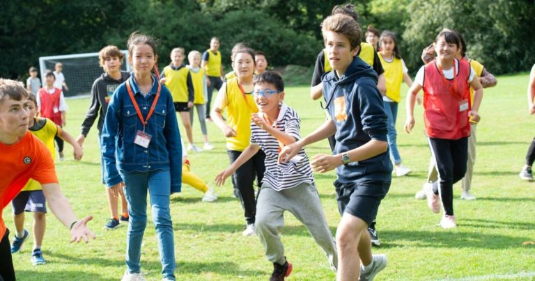 Um grupo grande de crianças fazendo esportes ao ar livre