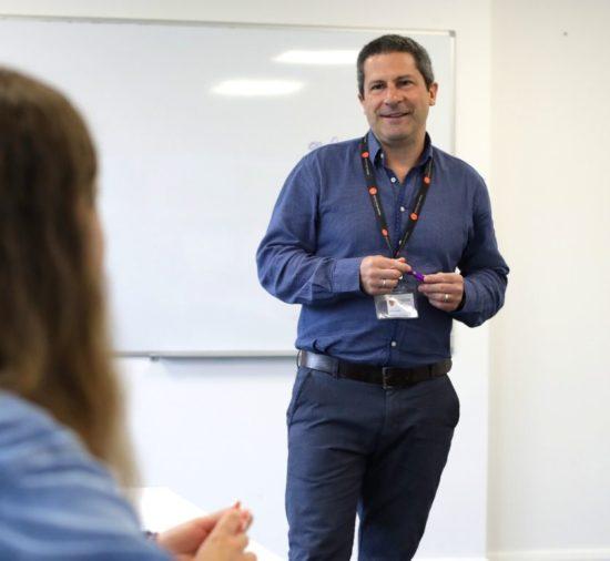 Professor na frente da sala de aula, com um quadro branco atrás dele, na BSC Dublin