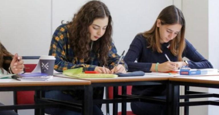 Duas meninas se inclinando sobre suas mesas em uma sala de aula na BSC Dublin