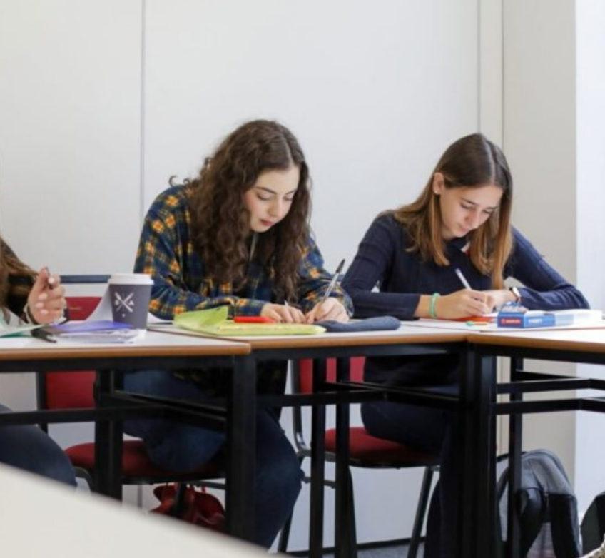Duas mulheres fazendo anotações em sala de aula.