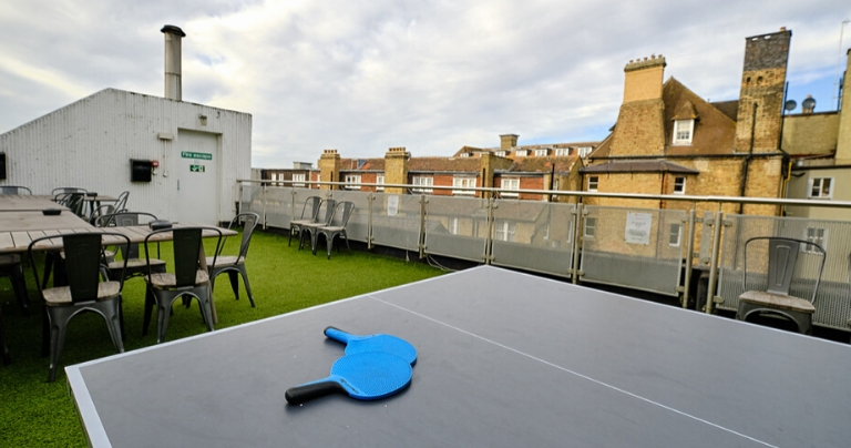 Área na cobertura da BSC Oxford, com mesa de ping pong e cadeiras