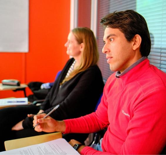 Dois alunos em sala ouvindo uma aula