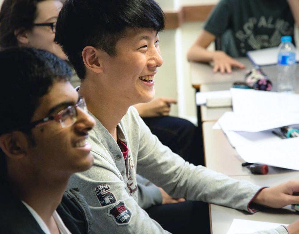 Estudantes do sexo masculino sorriem em uma sala de aula