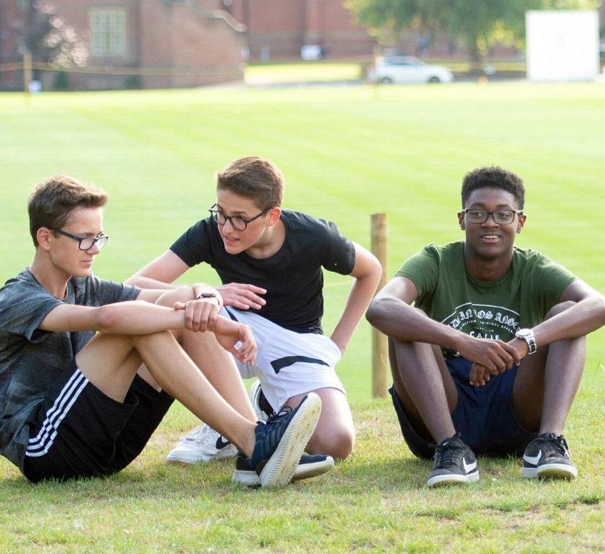 Três meninos em roupas esportivas, sentados na grama