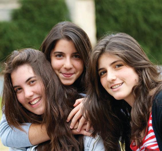 Três meninas se abraçando ao ar livre