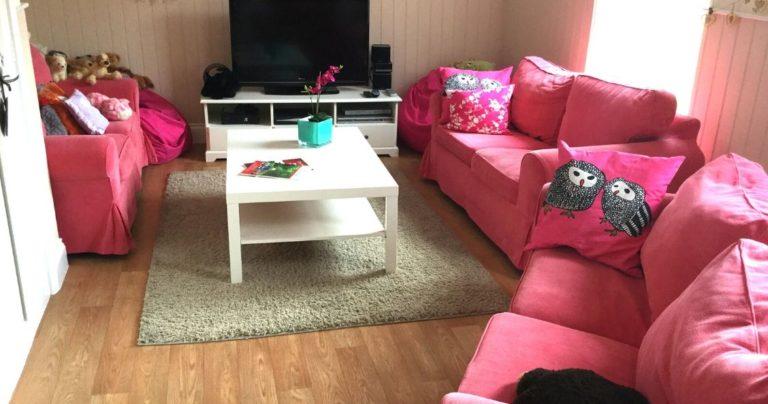 Uma sala de estar aconchegante com mobiliário cor-de-rosa