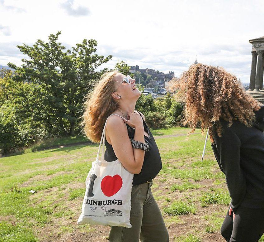 Estudantes rindo em um parque, segurando uma sacola de Edimburgo.