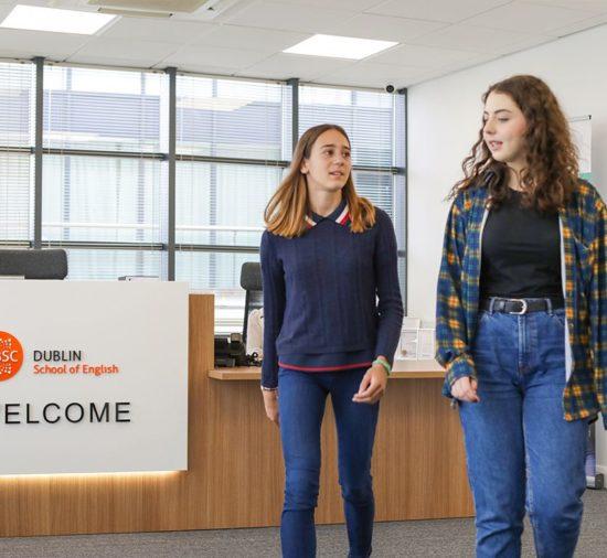 Duas jovens caminham passando pela moderna recepção na BSC Dublin