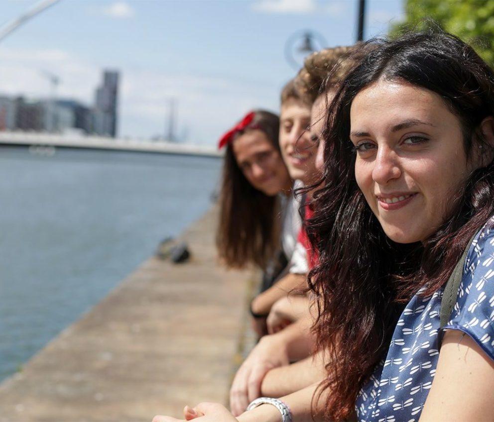 Alunos sorrindo ao longo do cais do rio Liffey