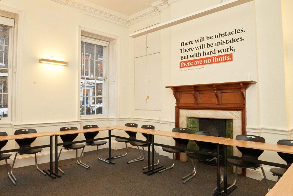 Mesas vazias em sala de aula na BSC Londres, com citações inspiradoras na parede