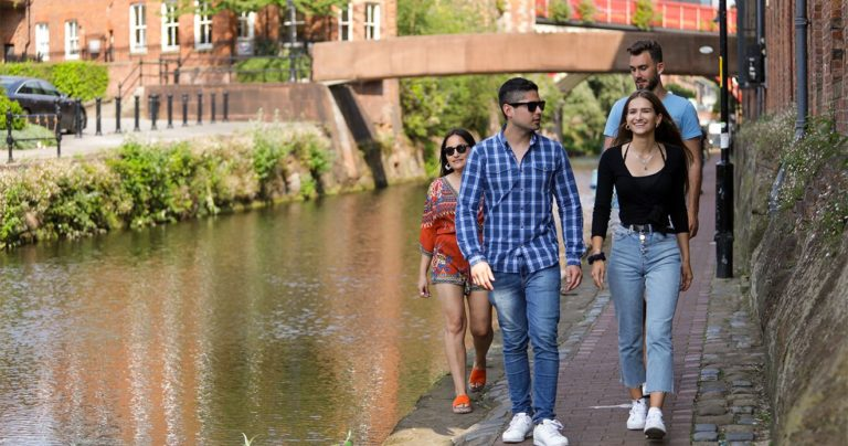 Alunos caminhando ao longo da margem do canal sob o sol