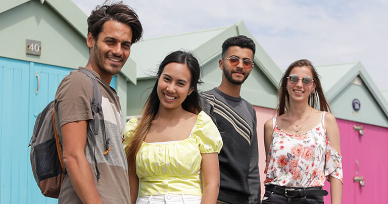 Quatro alunos em torno de vinte anos de idade na beira-mar em Brighton, em frente a algumas cabanas de praia coloridas