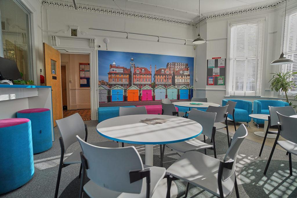 Centro de colaboração na BSC Brighton com uma foto de cabanas de praia na parede