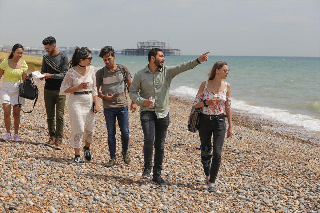 Um grupo de estudantes caminha pela praia de Brighton, apontando para o mar