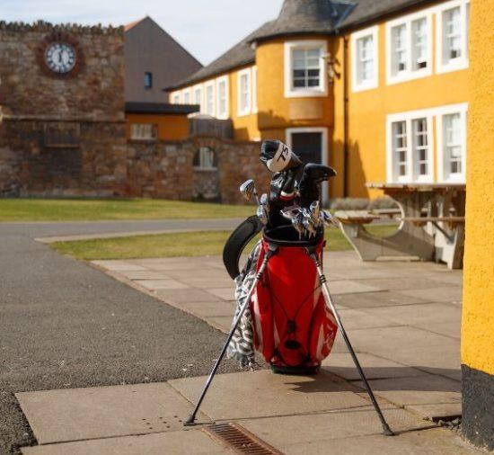 imagem de uma bolsa de golfe na área externas de edifícios da Loretto School