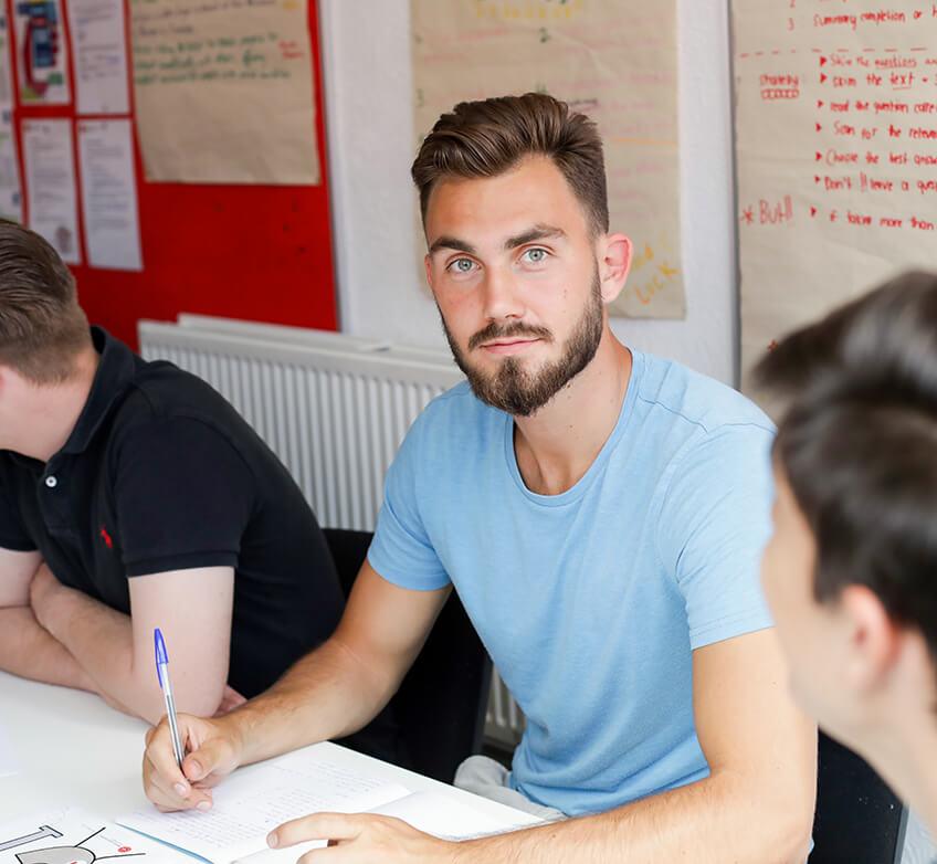 Aluno em sala de aula escrevendo