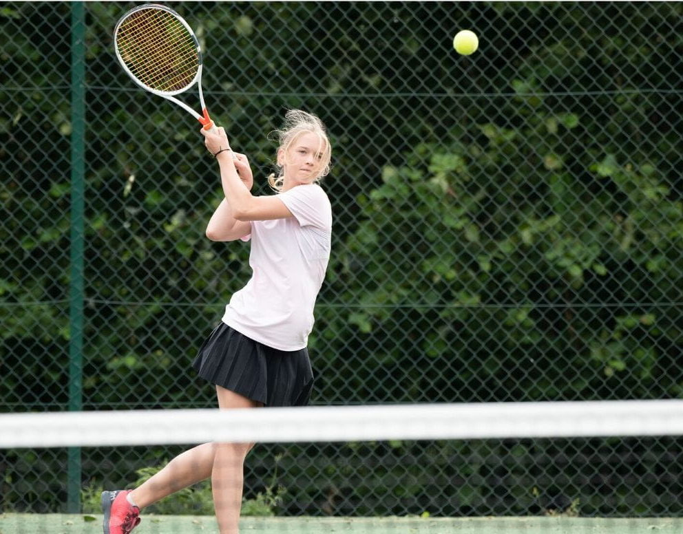 Uma jovem estudante com raquete de tênis se concentra para bater na bola que vem em direção a ela