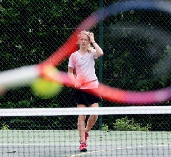 Uma jovem joga tênis em uma quadra no campos de verão