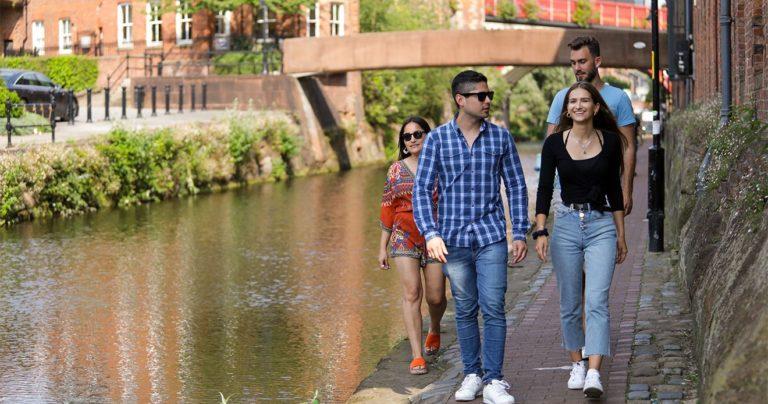 Studenti che passeggiano al sole lungo il canale