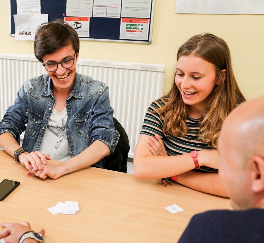 Двое учащихся смеются, занимаясь в классе