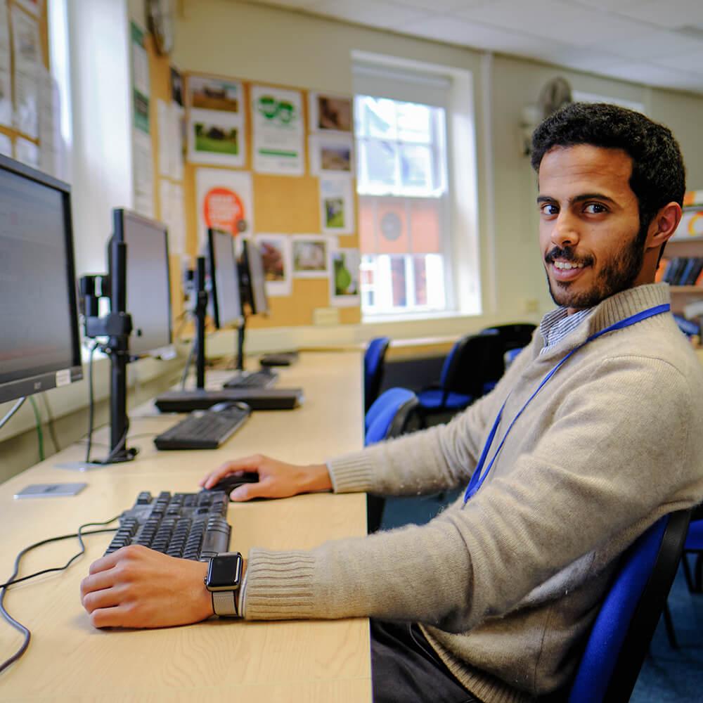 Молодой мужчина из Катара в зале Collaboration Hub школы BSC в Йорке пользуется компьютером.