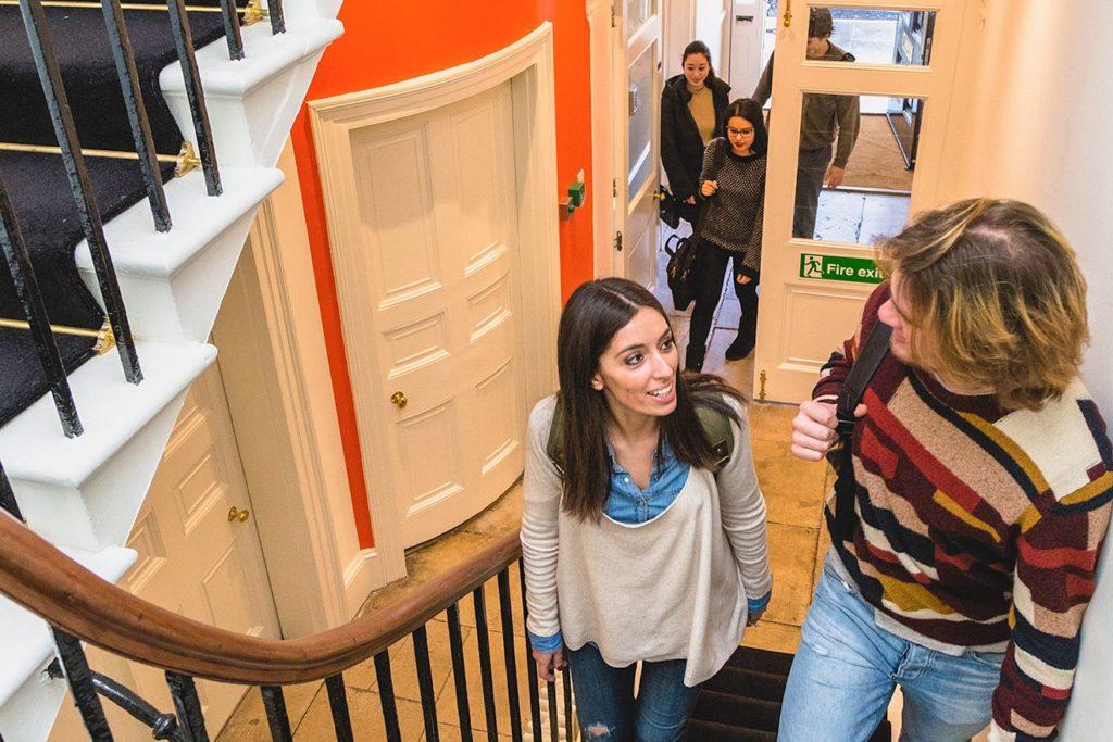 Учащиеся разговаривают, поднимаясь по лестнице, в школе BSC в Лондоне