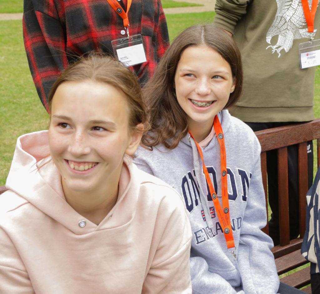 Молодые учащиеся сидят на скамье